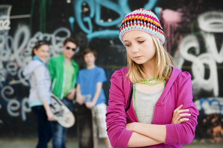 Teenagers standing in front of a wall with graffiti, a girl standing in the foreground