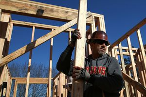Construction worker in hard hat carries lumber as he builds a new stick built home