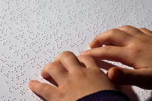 Young girl reading braille