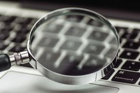 A magnifying glass above a MacBook keyboard