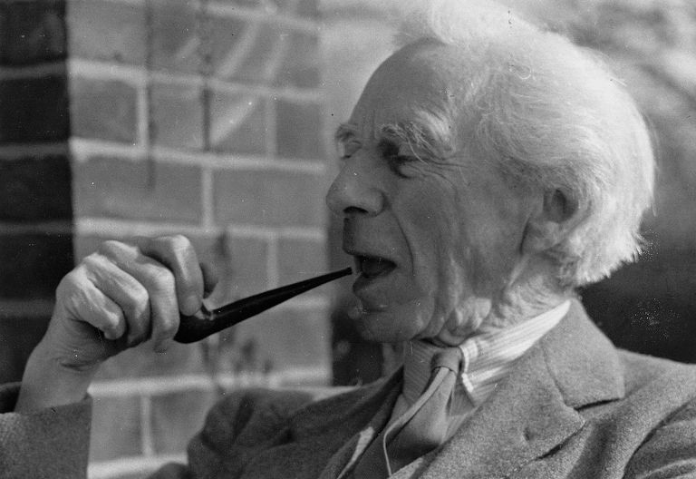 Bertrand Russell smoking a pipe and laughing