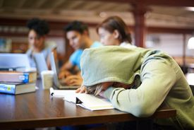 Student with head on desk sleeping in library