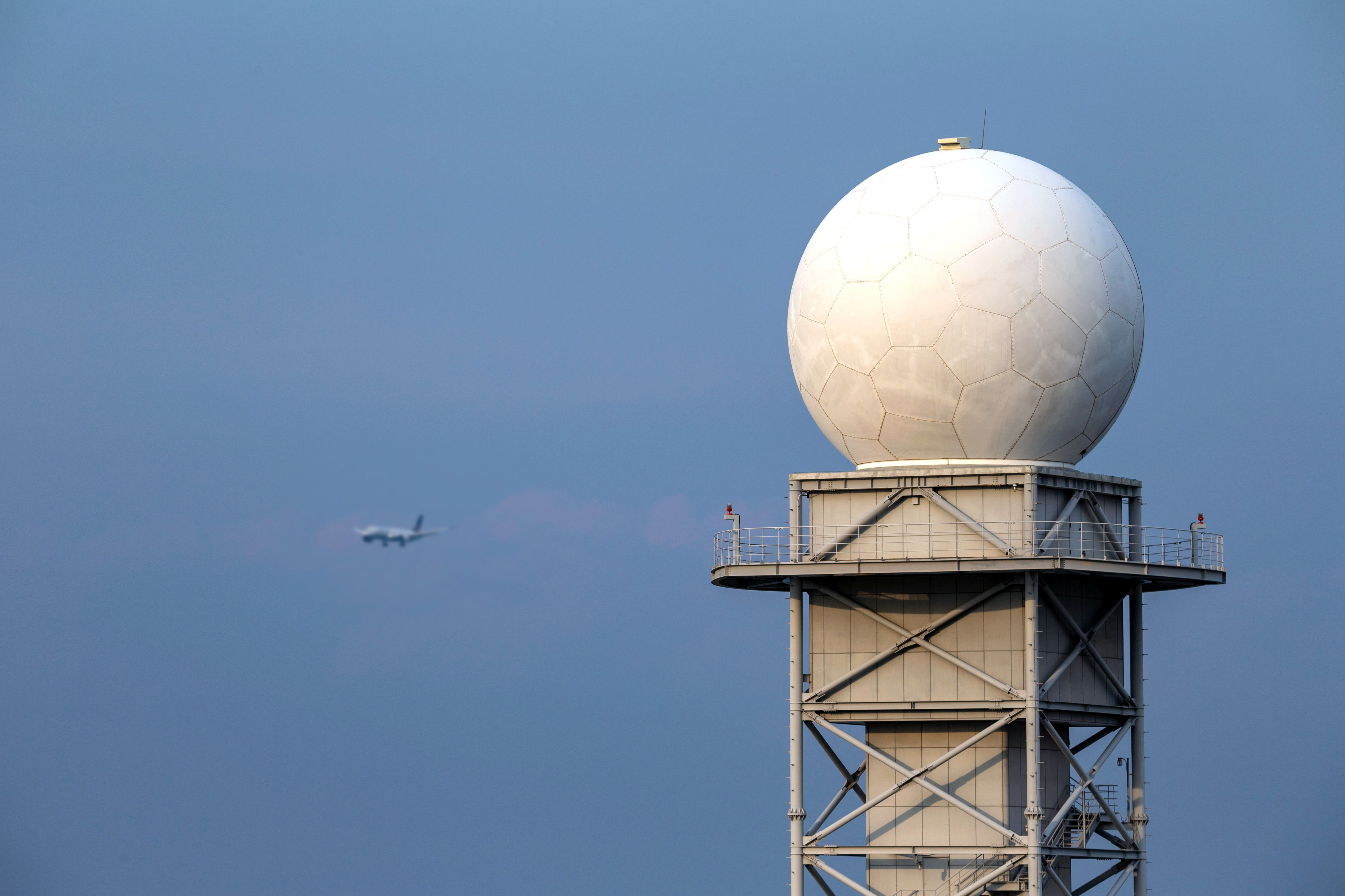 A weather radar with a blue sky and a plane in the background