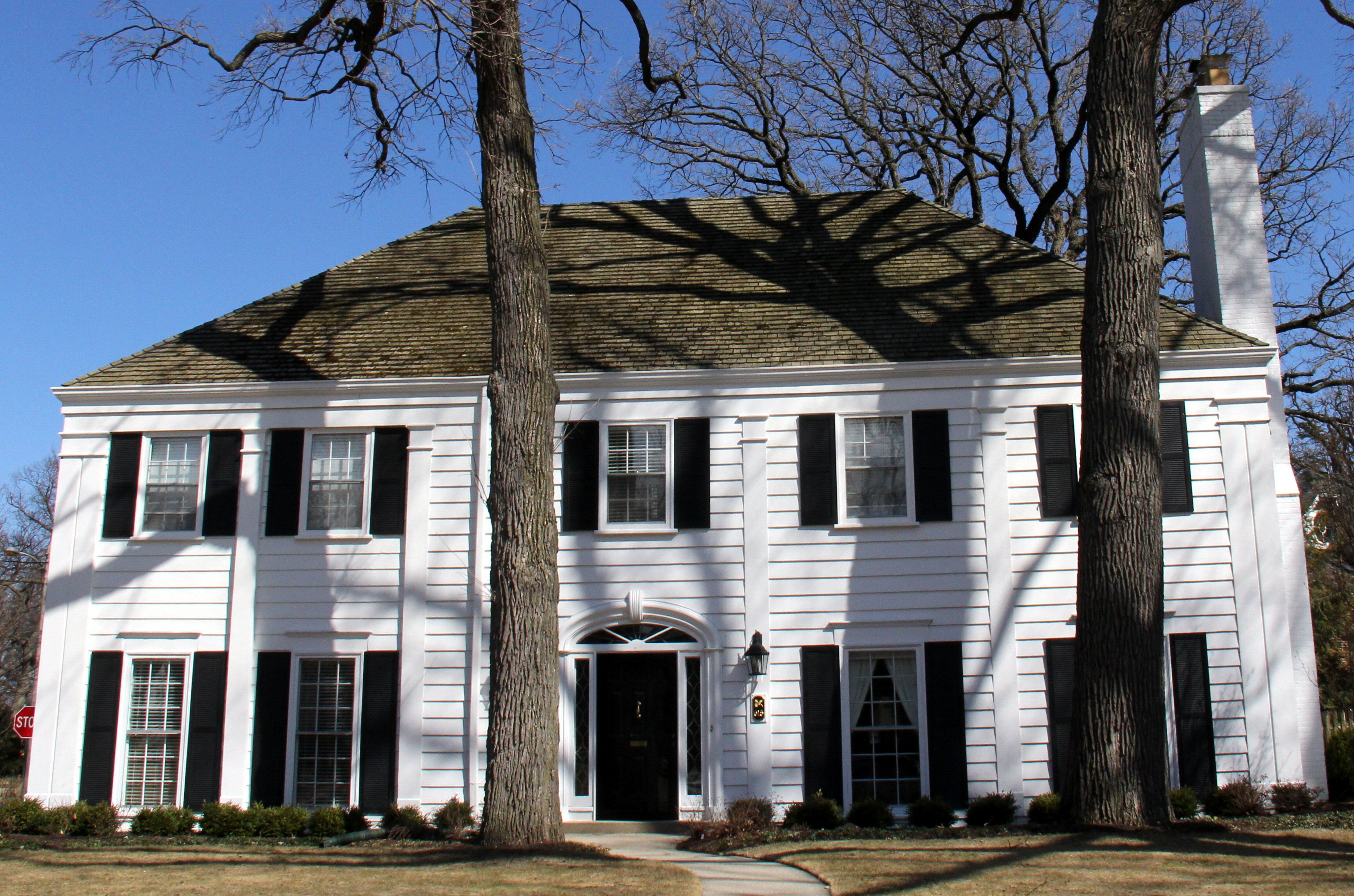 front of white house with hipped roof, black shutters, white chimney on right side, center front door, four evenly spaced pilasters across the facade reaching to corner pilasters on each end