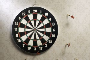 Darts in wall that missed dart board