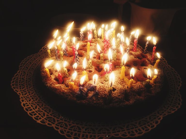 high angle view of lit candles on birthday cake on table