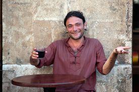 Italian man drinking wine at a sidewalk cafe