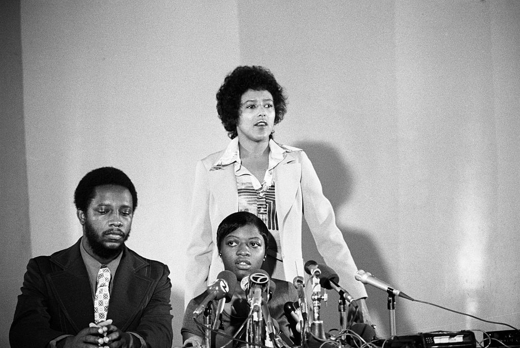 Elaine Brown next to Ms. Little and Larry Little at conference.