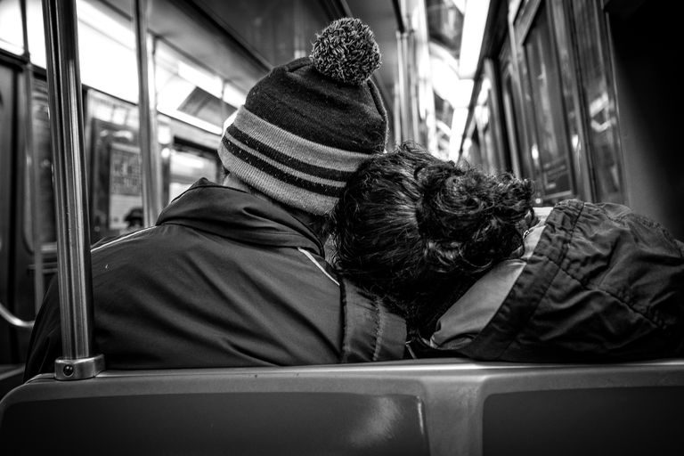 Rear View Of Couple Traveling On Subway Train