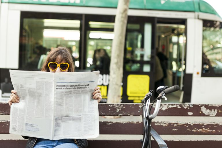 Woman wearing funny sunglasses reading newspaper on bench in the city