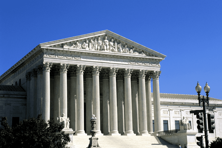 The classical columns of the Supreme Court Building set against a clear blue sky