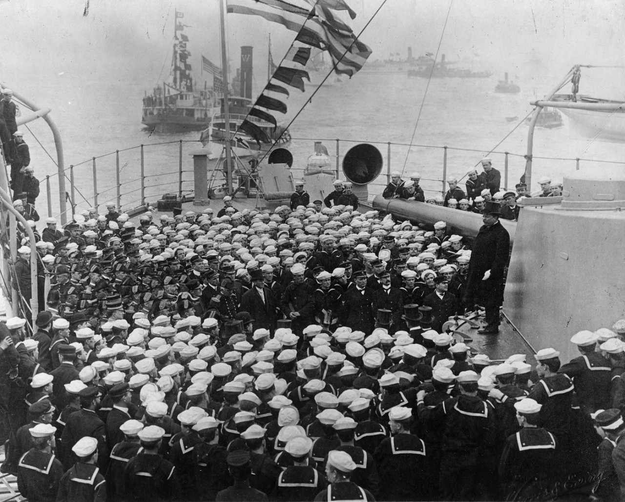 President Theodore Roosevelt standing on a battleship turret with a crowd of seamen in front of him.