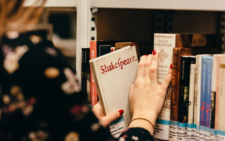 Woman with red nails taking a book of Shakespeare off a shelf.