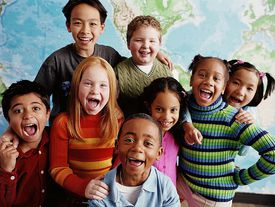 Smiling school children, members of the same age and educational cohort, pose in front of a world map