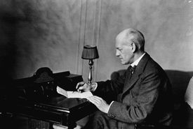 John Galsworthy writing with pen and paper at a desk