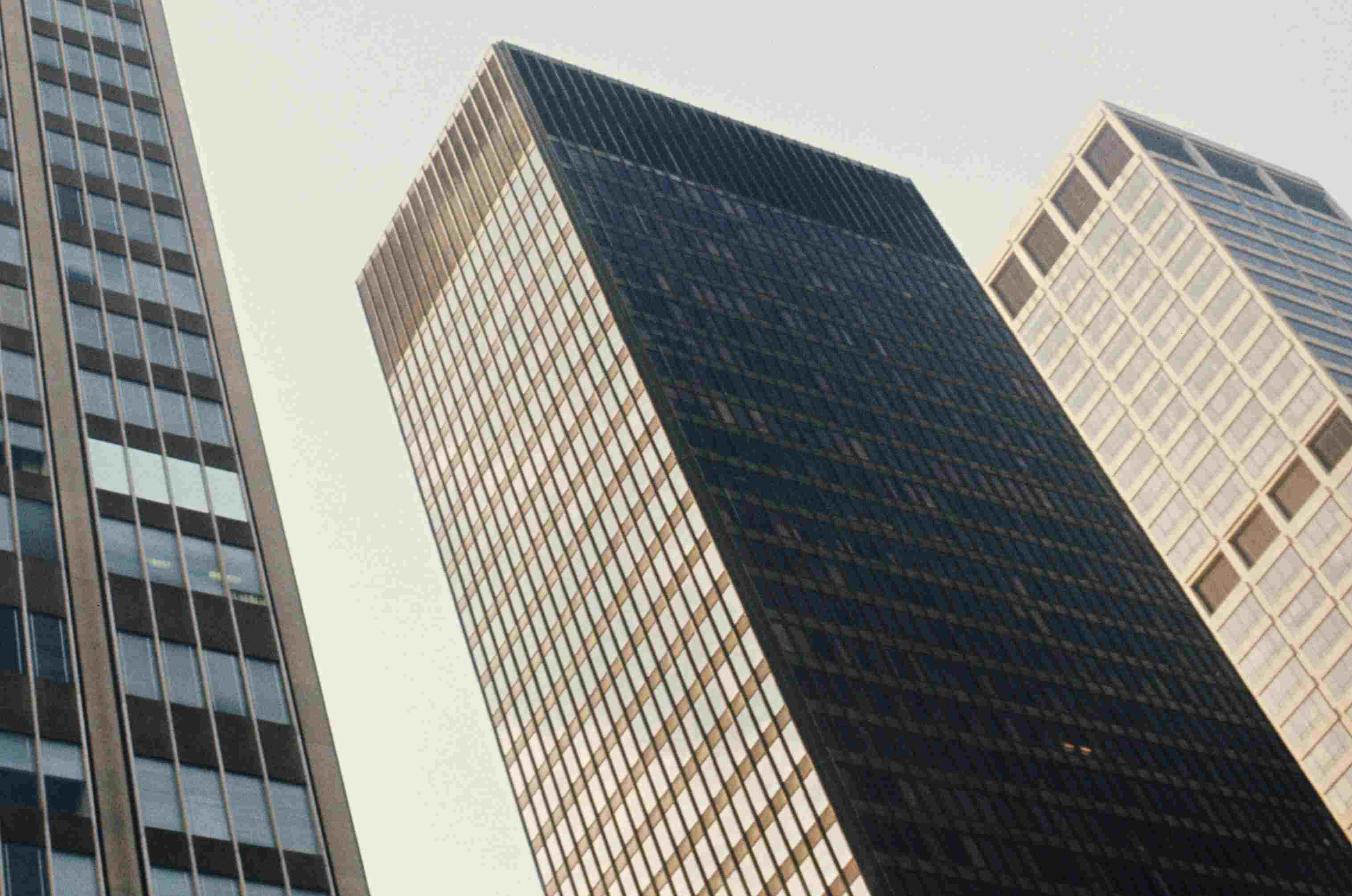 looking up at three skyscrapers, rectangular solids