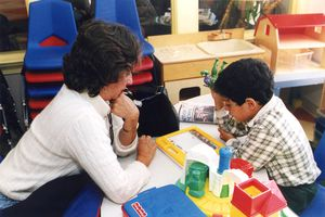 A teacher working with a student as both study an educational tool on a table.