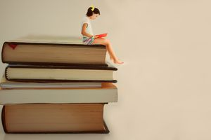 Girl sitting on an enlarged stack of books reading