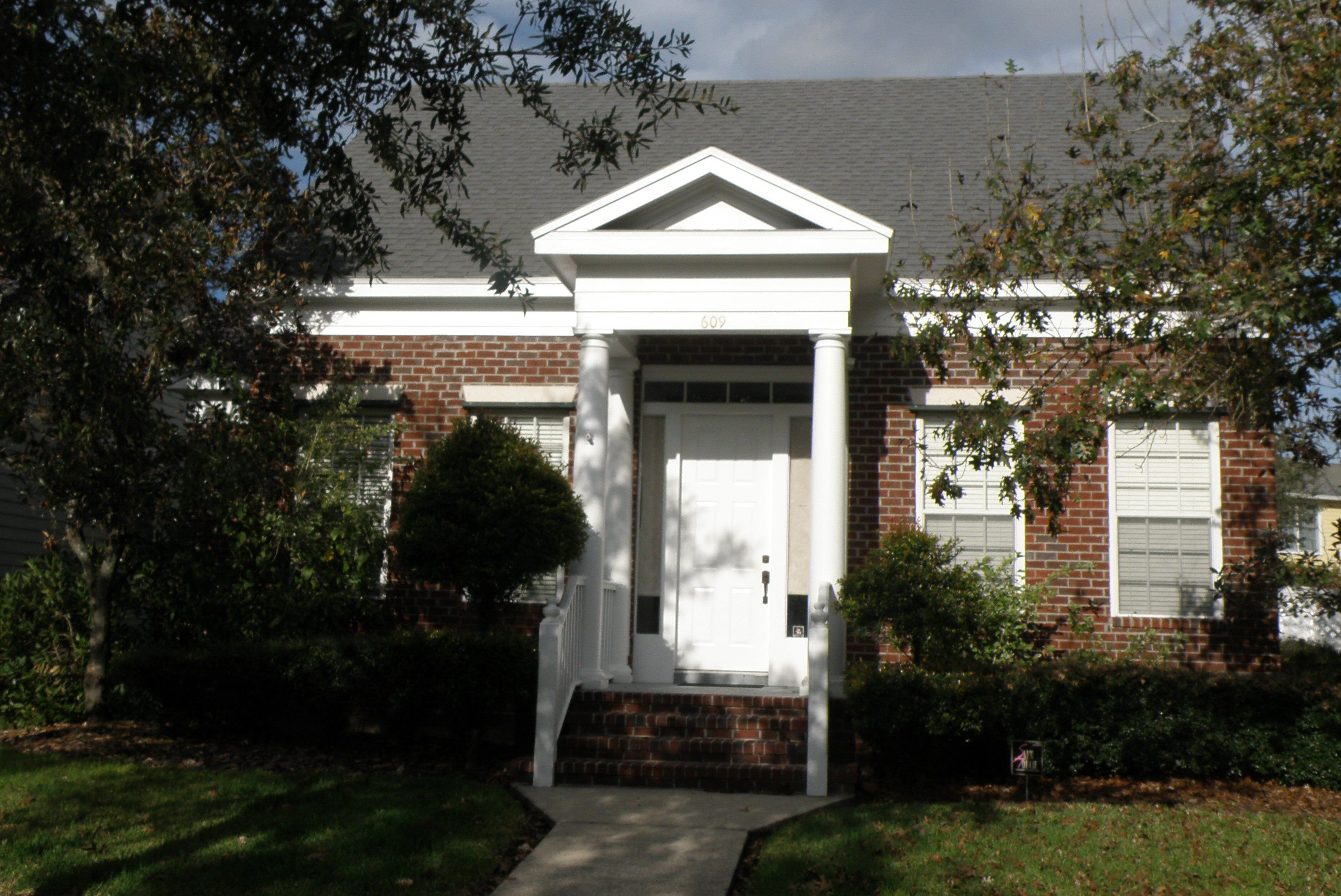 Small brick cottage with a narrow pediment front porch