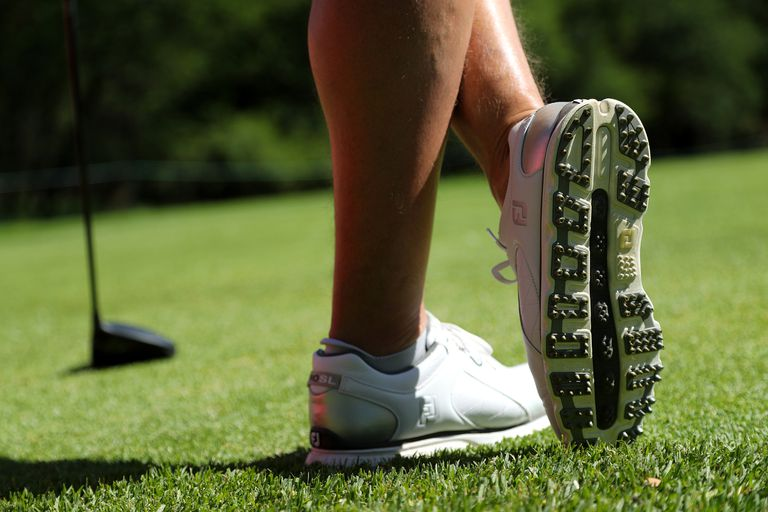 Detail of a pair of golf shoes as golfer waits on the tee.