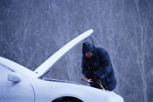 Man jump starting a car in snow