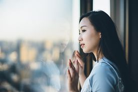 A woman looks outside a window at the city below her.