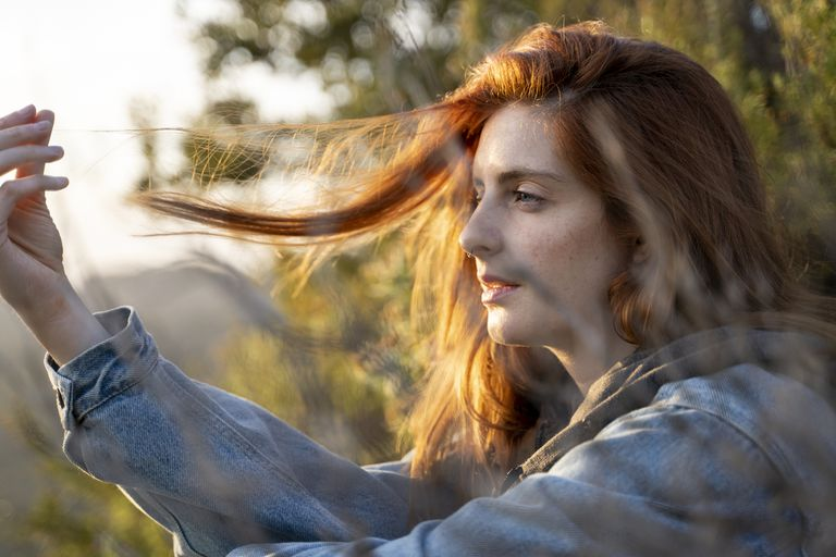 Redheaded young woman in nature at sunset