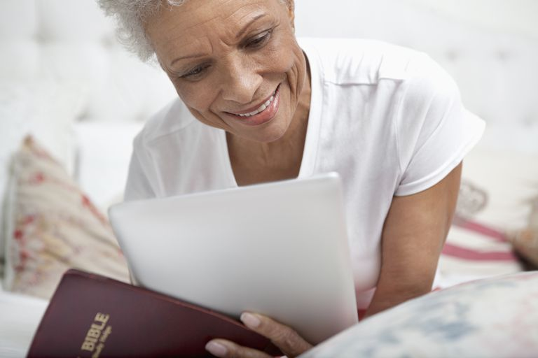 Older woman reading Bible and tablet.