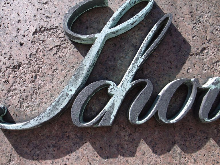 Scrollwork lettering on painted wood