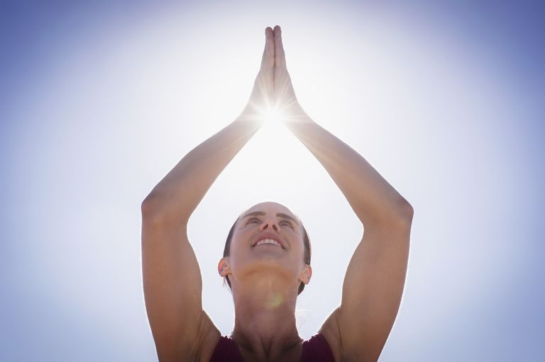 Caucasian woman holding hands clasped in sunshine in sky