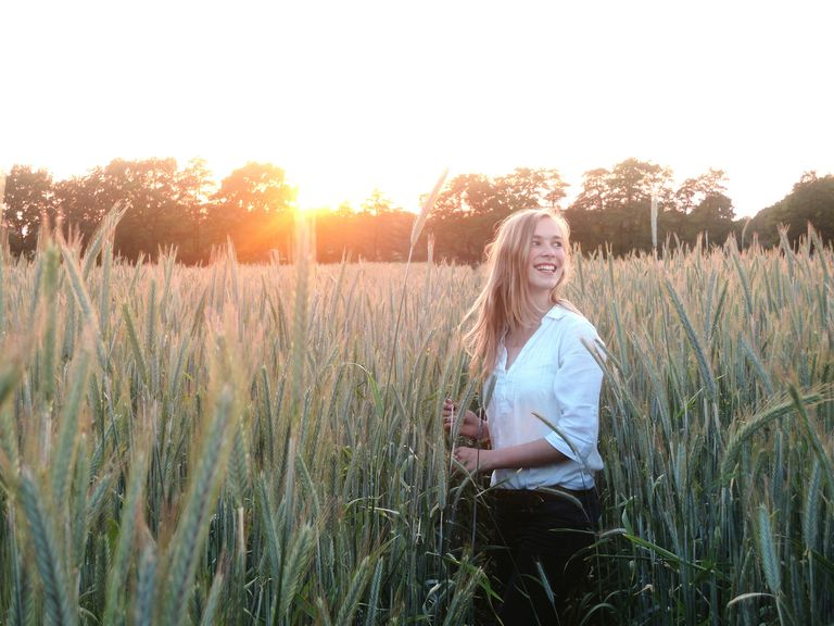 Happy Woman Standing Amidst Wheat Field Against Sky During Sunset