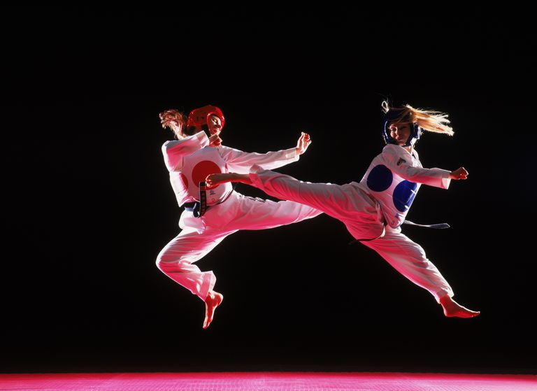 Tae Kwon Do, two women in mid-air jump kicking each other