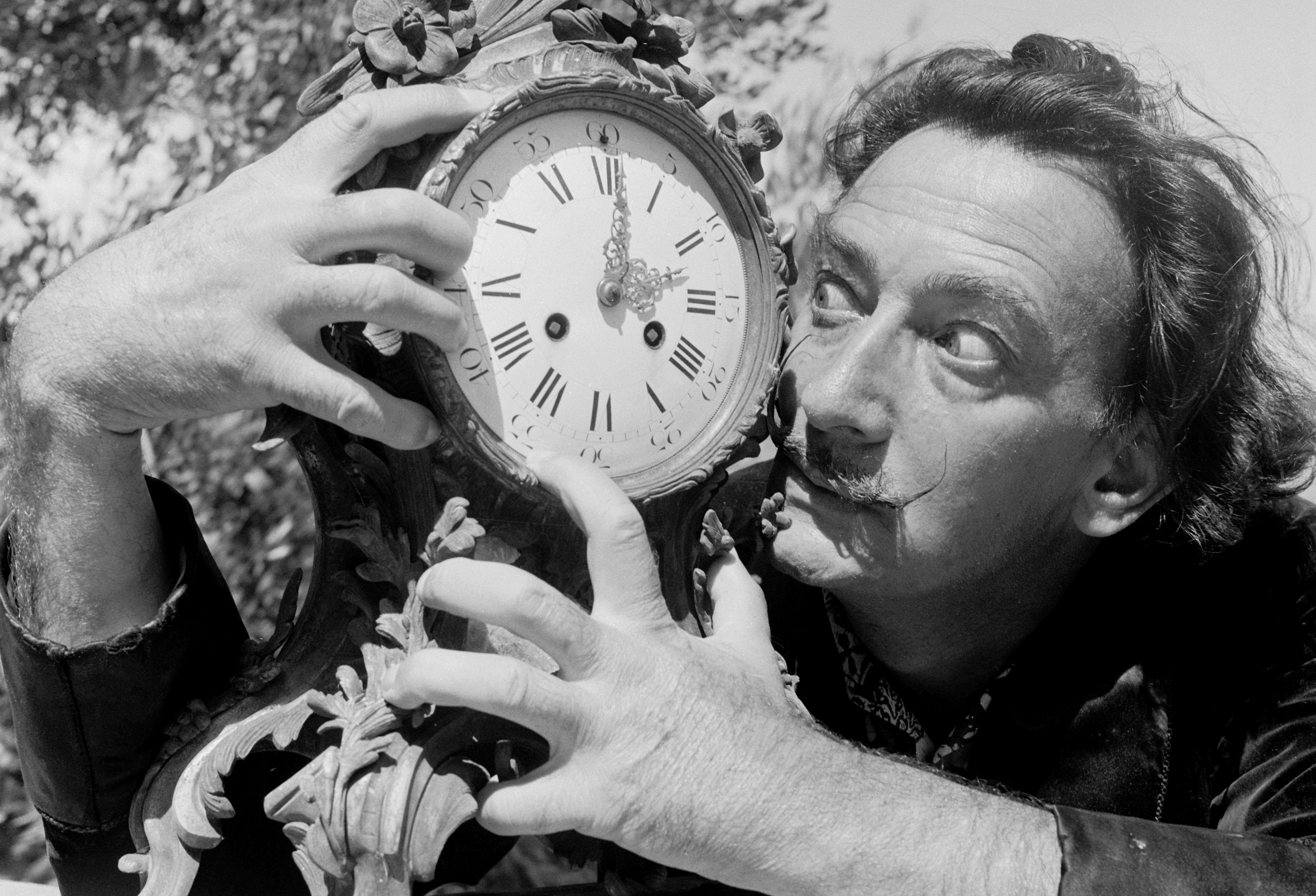 Black and white photograph of artist Salvador Dali clutching a clock