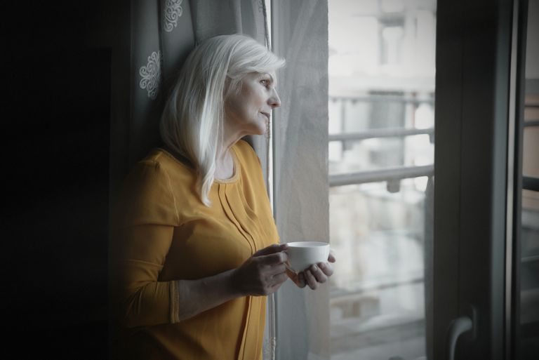 Regretful senior woman near window