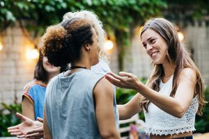 Two Young Women Greeting Each Other During Barbecue Meetup