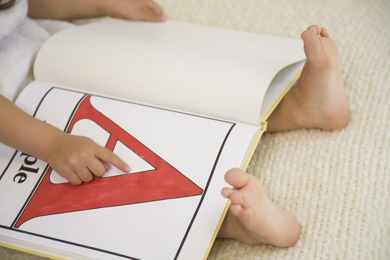 Young child pointing at the letter A in an alphabet book