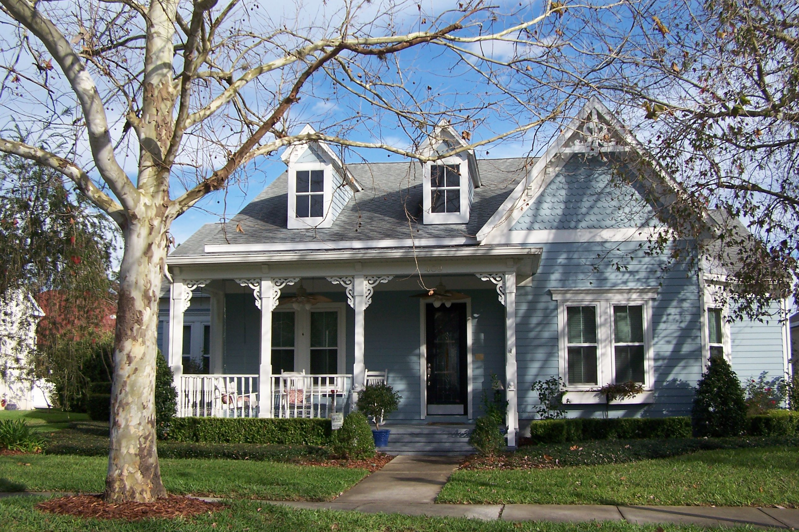 Blue-sided folk Victorian house with two dormers