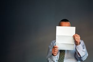 Man holding a piece of paper in front of his face, blocking our view