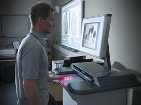 Man scanning fingerprint on machine with screen in laboratory