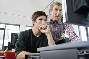 Instructor in computer class helping a student
