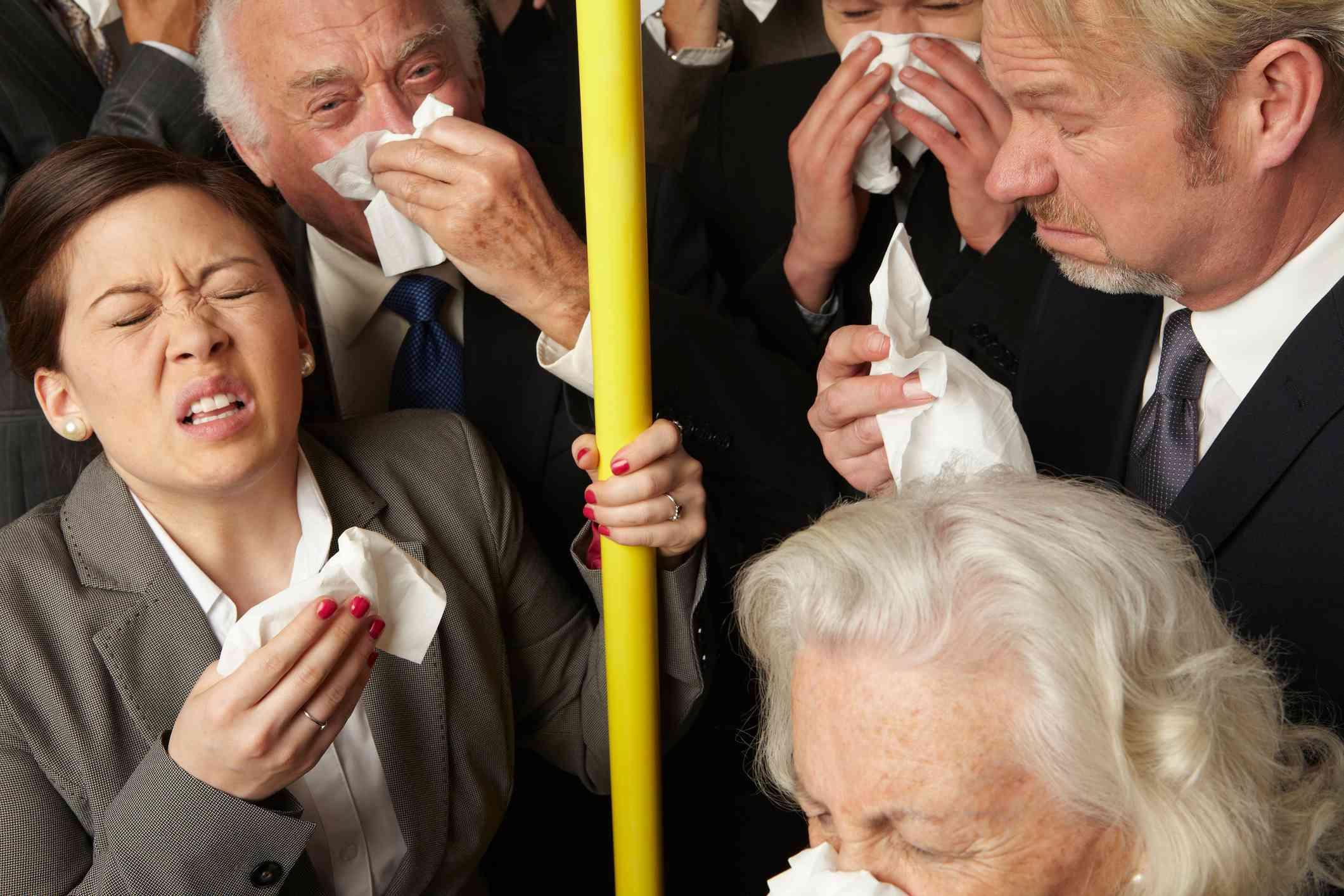 Businesspeople sneezing on subway train
