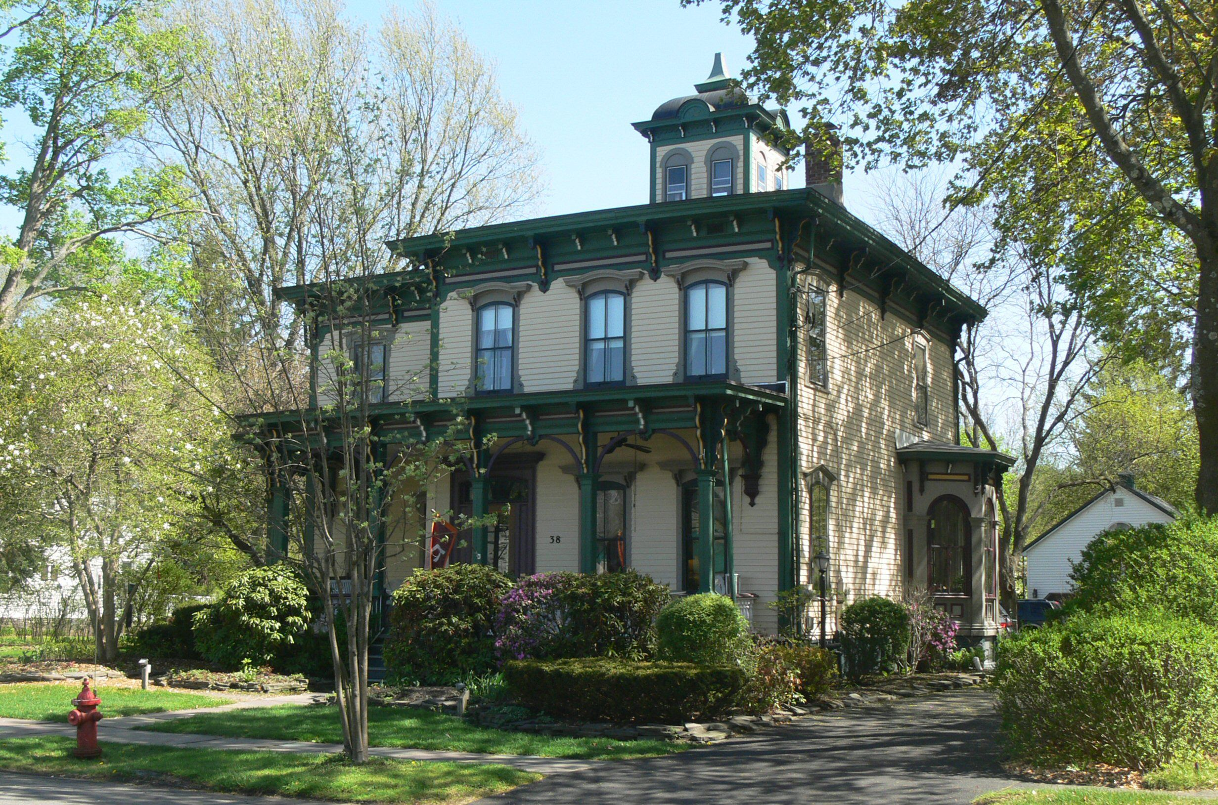two story, squarish house, flat roof with cupola, flat front porch roof, wide overhangs with brackets, trim colored green, siding cream-colored