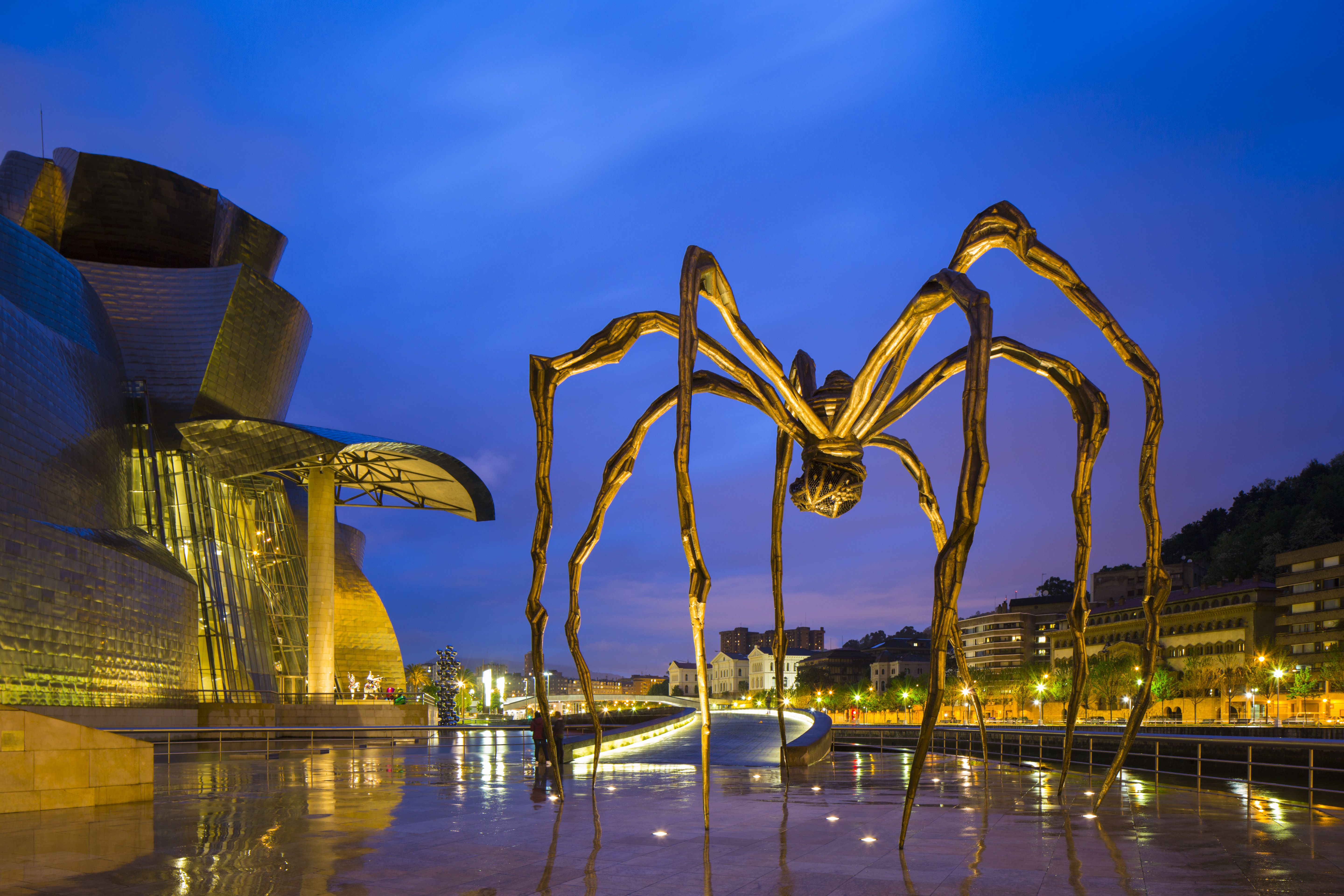 Huge spider sculpture by Louise Bourgeois illuminated at night