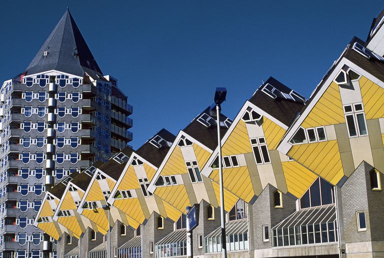 a row of yellow houses that look like yellow boxes turned on their angled side down -- next to a multi-sided round tower building with a pointed roof, like a pencil