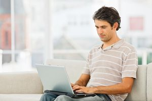 Young businessman sitting on couch and working on laptop