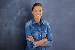 Portrait of a cheerful young woman standing against