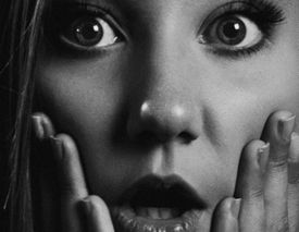 Close up of a shocked young woman's face, black and white photo.
