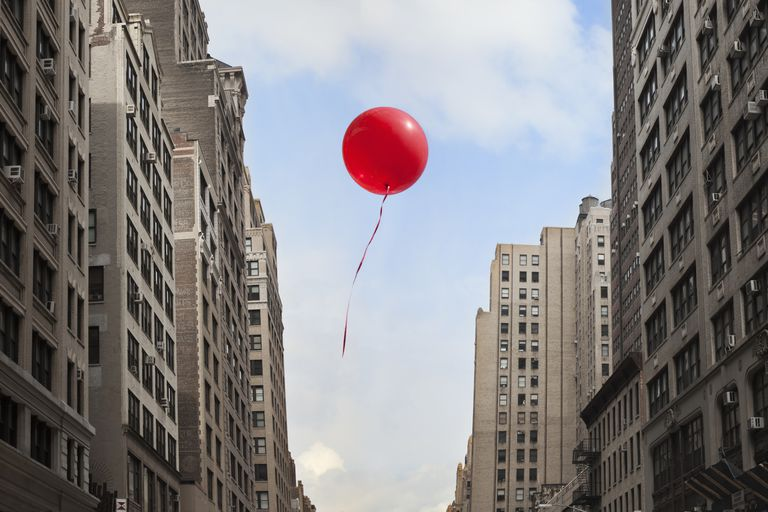 Red balloon floating between buildings