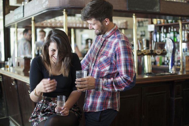 Man and woman laughing in a pub