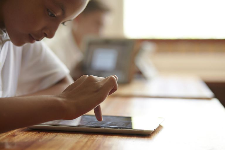 Close-up of schoolgirl scrolling on tablet